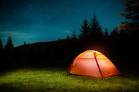 Illuminated tent in night forest