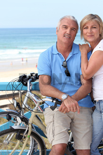A middle aged couple biking by the seashore.