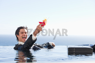 Delighted businessman relaxing in a swimming pool with a cocktai