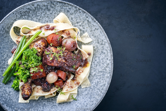 Modern style traditional French coq au vin with vegetable marinated in Burgundy sauce as top view in a design plate right