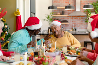 Diverse group of happy senior friends in holiday hats celebrating christmas together at home