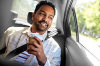 indian man with takeaway coffee on car back seat
