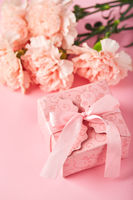 Bouquet of pink carnations and pink gift box. Design concept of holiday greeting with carnation bouquet on pink background