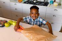 Happy african american boy unpacking groceries in kitchen