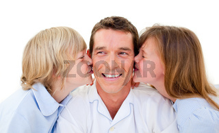 Cute siblings kissing their father against a white background