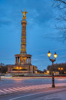 The famous Victory Column with a street light and tree branches in Berlin, Germany, at dusk