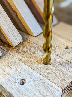 Drilling wooden plank close up