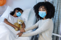 Mixed race mother and sick daughter in face masks in hospital, girl sleeping and holding teddy bear