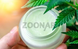 Hand holding Cannabis CBD lotion cream against Marijuana plant