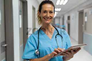 Portrait of mixed race female doctor stading on corridor smiling using laptop