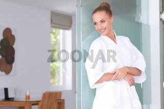 Beautiful woman standing in white bathrobe