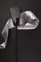 Black whip flogger and silver ribbon on leather background.