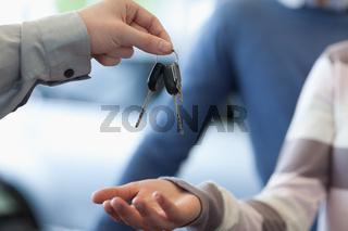 Car dealer giving keys to a customer