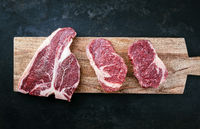 Raw dry aged wagyu porterhouse beef steak and entrecote offered as top view on wooden board with copy space