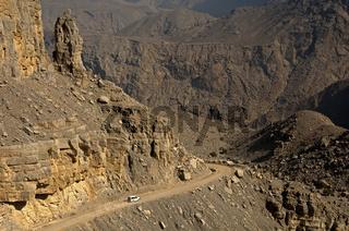 Weisses Geländefahrzeug auf einer Landstrasse in der wilden Berglandschaft auf der Auffahrt zum Jebel Harim
