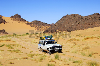 Geländefahrzeug mit Touristen auf einer sandigen Wüstenpiste