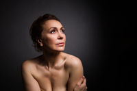 portrait of a sensual fifty year old woman on grey studio background