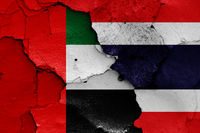 flags of UAE and Thailand painted on cracked wall