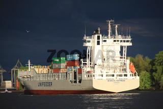 Containerschiff vor dunklem Himmel