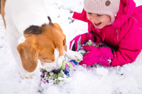 Child playing with dog on snow.