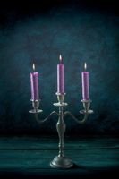 Magic candles in a vintage candle holder, side view on a dark background