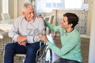 Lächelnder Mann kümmert sich um Senior Mann im Rollstuhl