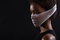Closeup portrait of african american woman fashion model wearing quarantine medical face mask coarse mesh net on black background. Covid-19 coronavirus protection concept.
