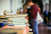 Stack of books at a charity book flea market, text space