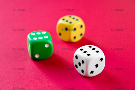 Three colorful dices isolated on pink background