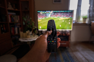 A hand pointing remote control at tv or television set with soccer or football match indoors, point of view, wide angle with selective focus.