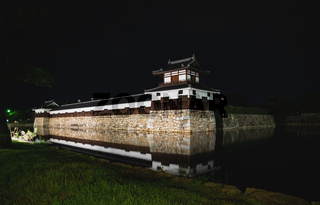The illuminated fortress walls of Hiroshima castle surrounded by water in the night, Hiroshima, Japan