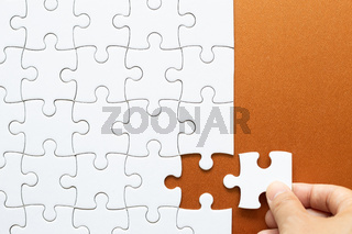 Set of white puzzle pieces and hand holding last one piece