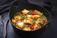 Modern style traditional Spanish seafood zarzuela de pescado with fish served in red sauce as close-up in design pot