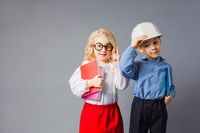 The little couple in costumes of teacher and engineer
