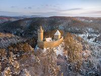 Aerial view of medieval castle Kokorin in winter during sunrise. National park Kokorinsko nearby Prague in Czech Republic. Central Europe.