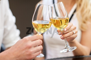 close up of couple clinking wine glasses