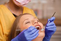 Beautiful young blonde women teeth being checked at dentistry