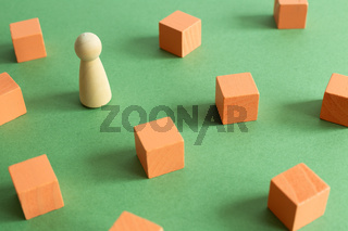 Group of coral blocks and one different wooden human figure on green background. Different opinion, direction, idea, innovation concept