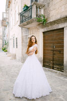 The bride in tender wedding dress stands near beautiful ancient building in Perast