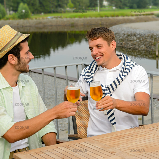 Cheerful male friends drinking beer at pub