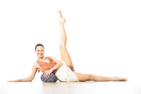 Young sporty healthy woman in bright white yoga studio, lying on bolster cushion, stretching, smilling, showing love and passion for bolster yoga.