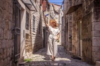 Beautiful blonde young female traveler wearing straw sun hat, taking selfie while sightseeing and enjoying summer vacation in an old traditional costal town at Adriatic cost, Croatia.