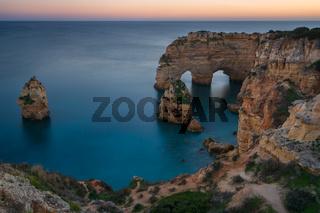 Natural arch cliffs of Praia da Marinha beach at sunset beautiful landscape with atlantic ocean, in Lagoa Portugal