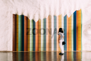 Woman looking at tile colorful pattern in T-Centralen Stockholm underground
