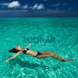 Woman in bikini lying on water