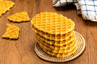 High angle view stack of homemade crispy waffles on bamboo mat.