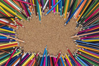 Background photo of colored pencils on a cork plate
