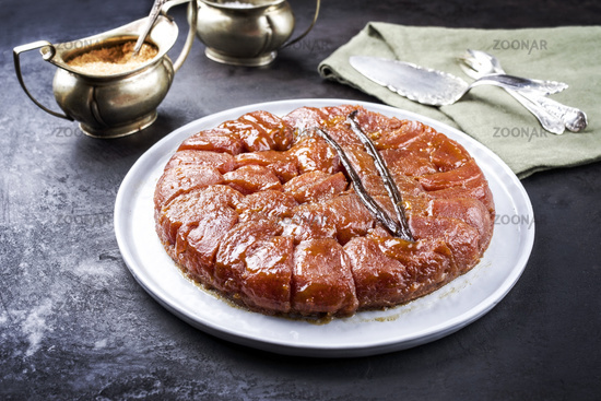 Traditional French tarte tatin with apples and vanilla offered as close-up on a modern Nordic design plate with rustic background