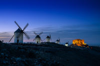 A view of the windmills and castle of Consuegra in La Mancha in central Spain at nightfall