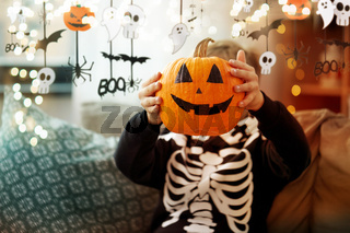 boy in halloween costume with jack-o-lantern